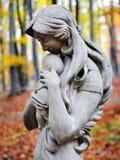 Madonna雕象和子项在秋天森林里 免版税库存照片