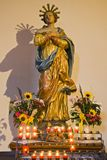 Madonna. An Altar with Madonna in a church, surrounded by candles and flowers Royalty Free Stock Images