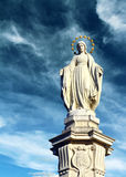Madonna. Figure of the Madonna on a pedestal in the crown of gold, against a blue cloudy sky Royalty Free Stock Image