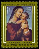 Madonna And Child Postage Stamp From Guinea-Bissau. A vintage postage stamp from Guinea-Bissau depicting Madonna and child from artist Raffaello (Raphael) royalty free stock images