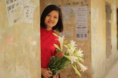 Beautiful girl in red traditional dress bring madonna lily flower in her hand royalty free stock photography