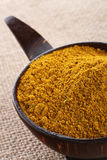 Madras Curry Powder in bowl hessian background. Madras Curry Powder in coconut bowl, on brown hessian background, shallow DOF royalty free stock photo