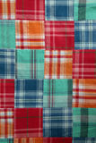 Madras plaid quilt. Cotton squares of fabric making a summery plaid quilt Royalty Free Stock Image