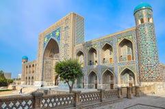 Madrasah Sher-Dor i den Registan fyrkanten, en sidosikt Arkivbild