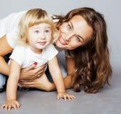 Madre abbastanza alla moda con la piccola figlia bionda sveglia che abbraccia, famiglia sorridente felice, concetto dei giovani d Immagine Stock Libera da Diritti