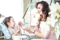 Madre abbastanza giovane che alimenta il suo bambino caro Fotografia Stock