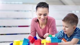 Madre adorable feliz del primer medio que goza jugando los cubos de los juguetes del juego con poco hijo lindo almacen de metraje de vídeo