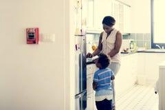 Madre africana con suo figlio nella stanza della cucina fotografia stock libera da diritti