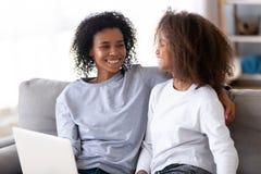 Madre africana e hija que se sientan en el sofá usando el ordenador imagen de archivo