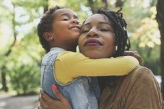 Madre afroamericana che abbraccia la sua piccola figlia in prato fotografie stock libere da diritti