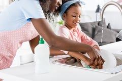 madre afroamericana e figlia che lavano i piatti con il detersivo fotografia stock libera da diritti
