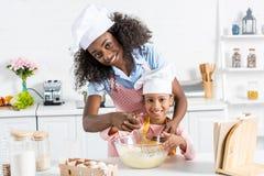 madre afroamericana e hija en los sombreros del cocinero que mezclan la pasta con el batidor fotos de archivo