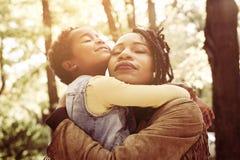 Madre afroamericana e sua la figlia che abbracciano con la figlia i Fotografia Stock