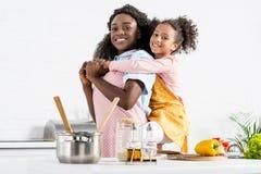 madre afroamericana felice che trasporta sulle spalle figlia fotografia stock