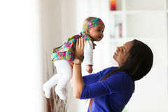 Madre afroamericana joven que juega con su bebé foto de archivo