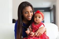 Madre afroamericana joven que juega con su bebé Imágenes de archivo libres de regalías