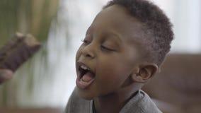Madre afroamericana que juega y que se divierte con el hijo lindo que le da el pedazo del chocolate de torta Mam? de la relaci?n  almacen de metraje de vídeo