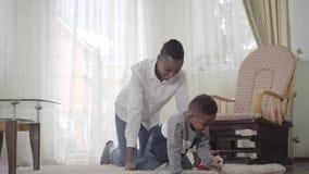 Madre afroamericana smilling hermosa con su pequeño muchacho lindo del niño que se divierte así como pequeñas danzas en acogedor almacen de metraje de vídeo