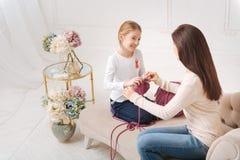 Madre agradable feliz que enseña a su hija a hacer punto fotos de archivo libres de regalías