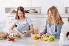 Madre agradable y su hija adolescente que cocinan la ensalada vegetal Imagenes de archivo