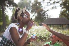Madre al aire libre que muestra a pequeñas hijas el jardín imagen de archivo