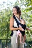 Madre alegre con el bebé en honda imagen de archivo
