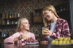 madre alegre e hija que desayunan junto Imágenes de archivo libres de regalías