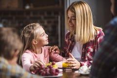 madre alegre e hija que desayunan junto Imagenes de archivo