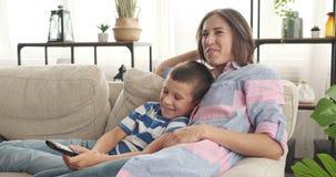 Madre alegre e hijo que ven la TV en casa almacen de video