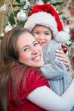 Madre alegre que abraza a su hijo en la Navidad Fotos de archivo