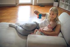 Madre alegre que juega con su bebé en casa fotografía de archivo
