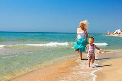 Madre alegre y bebé que corren en resaca en la playa Foto de archivo libre de regalías