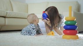 Madre alegre y bebé que juegan con los juguetes en una alfombra en casa Vista lateral de una madre y de un hijo felices que juega almacen de video