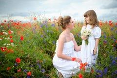 Madre alegre y su hija con un ramo de las flores salvajes  Foto de archivo
