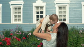 Madre allegra che solleva figlia allegra nel giardino stock footage