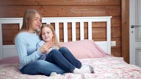 Madre allegra della foto a figura intera giovane che gode della rottura che abbraccia la sua piccola figlia a mano a casa interni video d archivio