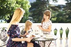 Madre allegra e figlia che si siedono al caffè di aria aperta mentre drin Immagine Stock