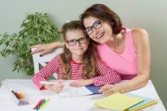 Madre amorosa che aiuta il suo decreto dell'allievo della scuola elementare della figlia Fotografie Stock Libere da Diritti