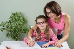 Madre amorosa che aiuta il suo decreto dell'allievo della scuola elementare della figlia Fotografia Stock