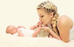 Madre amorosa che bacia il bambino dei piedi sulla casa del letto Fotografia Stock