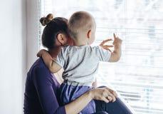 Madre amorosa che gioca con il suo fare da baby-sitter su una finestra Essi che aspettano qualcosa fotografie stock