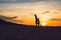Madre apta con el hijo que corre en el desierto en Gran Canaria, Maspalomas en puesta del sol Foto de archivo