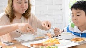 Madre asiática con el hijo que come el almuerzo en casa almacen de metraje de vídeo