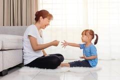 Madre asiática e hija chinas que juegan piedra papel o tijera imagen de archivo libre de regalías