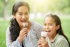 Madre asiática e hija que comen el helado en parque fotos de archivo libres de regalías