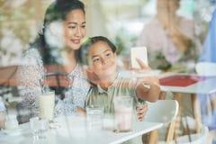 Madre asiática e hija que toman el selfie en café imágenes de archivo libres de regalías