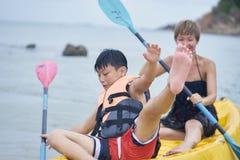 Madre asiática e hijo que juegan kayaking en el mar durante las vacaciones en que equilibrio perdidoso del niño fotos de archivo