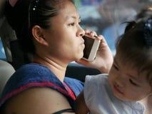 Madre asiática incómodo que hace una llamada de teléfono mientras que trata de su hija en un coche de conducción fotos de archivo