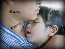 Madre asiática que celebra a su hija durmiente, mientras que se preocupa de la salud, de la ropa, de la escuela, y de la segurida fotos de archivo
