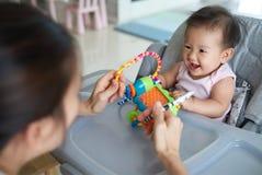 Madre asiática que juega el juguete con su bebé que se sienta en la silla dinning imagen de archivo
